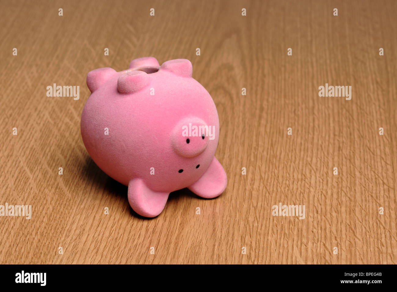 Upside down piggy bank - Stock Image