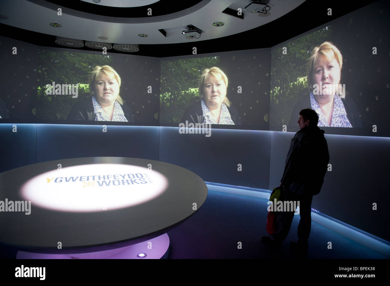 a person looking at audio-visual story-telling display at THE WORKS exhibition and cultural centre, Ebbw Vale , - Stock Image