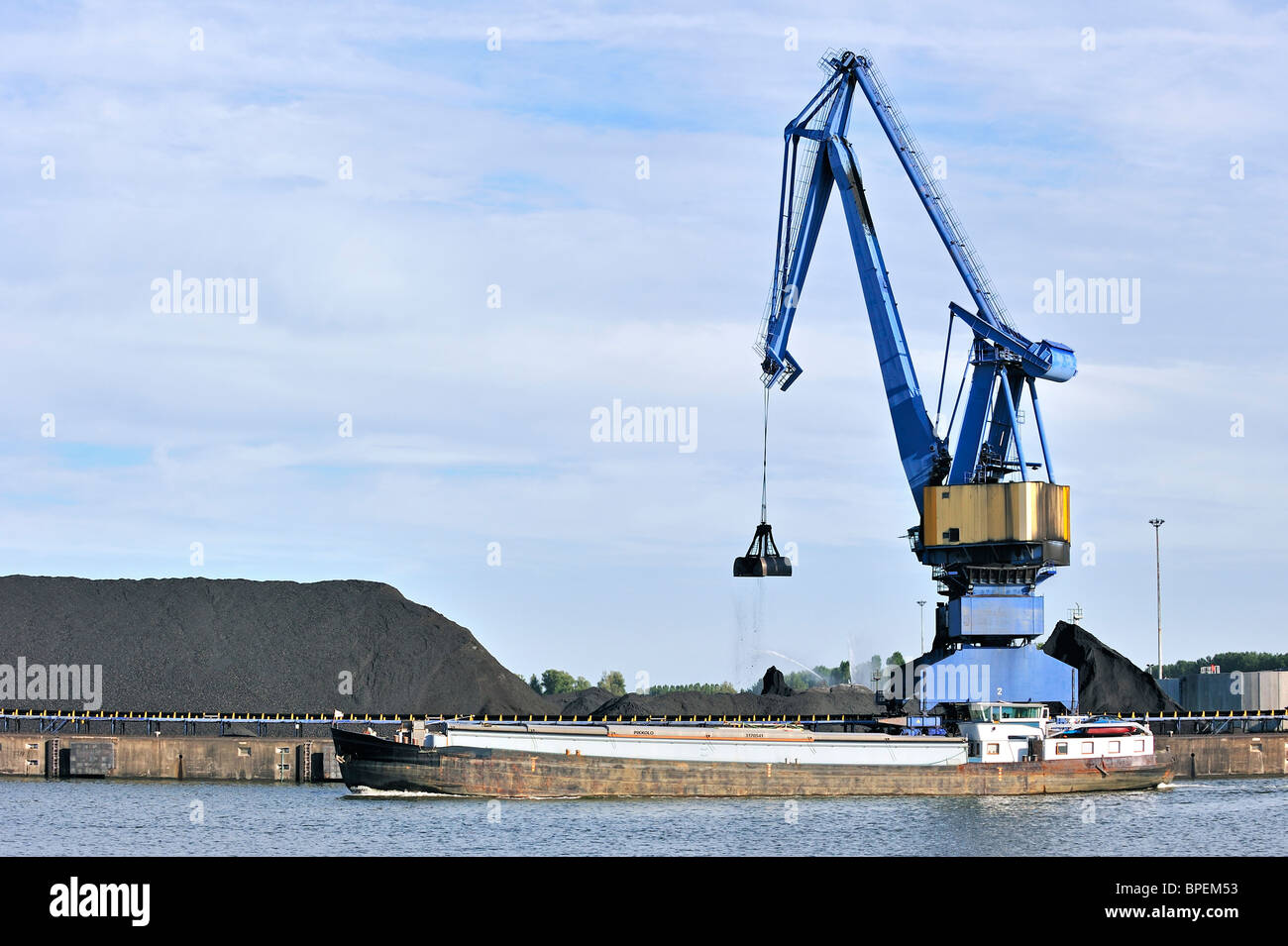Dock crane loading coal / ore in inland vessel at Ghent seaport, Belgium - Stock Image