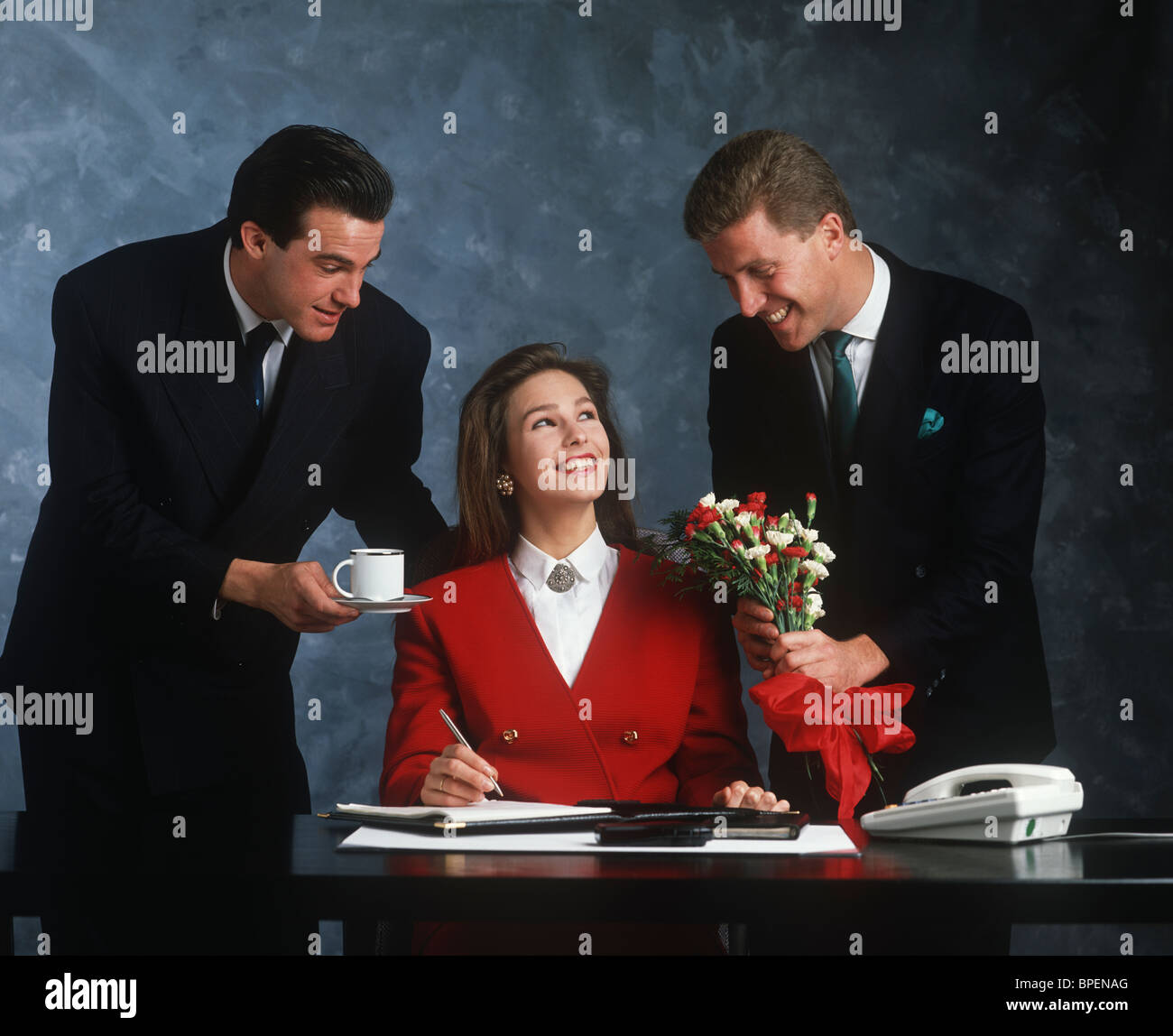 Two men and a woman in an office situation - Stock Image