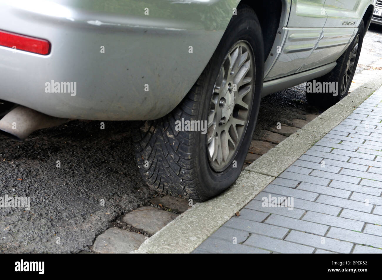 Bad car parking with part of the rear tyre on the pavement. - Stock Image