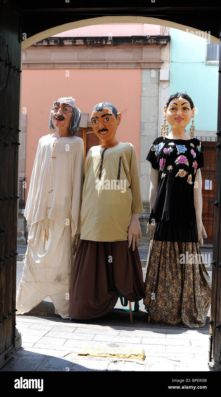 Three traditionally dressed artist's models displayed at the entrance to a modern art museum in central Oaxaca, - Stock Image