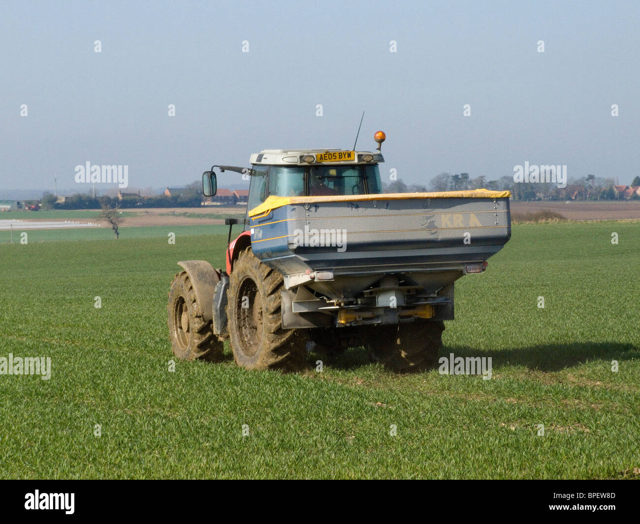 Massey Ferguson 6480 tractor fitted with KRA fertilizer spreader working in a wheat field on a sunny April day in - Stock Image