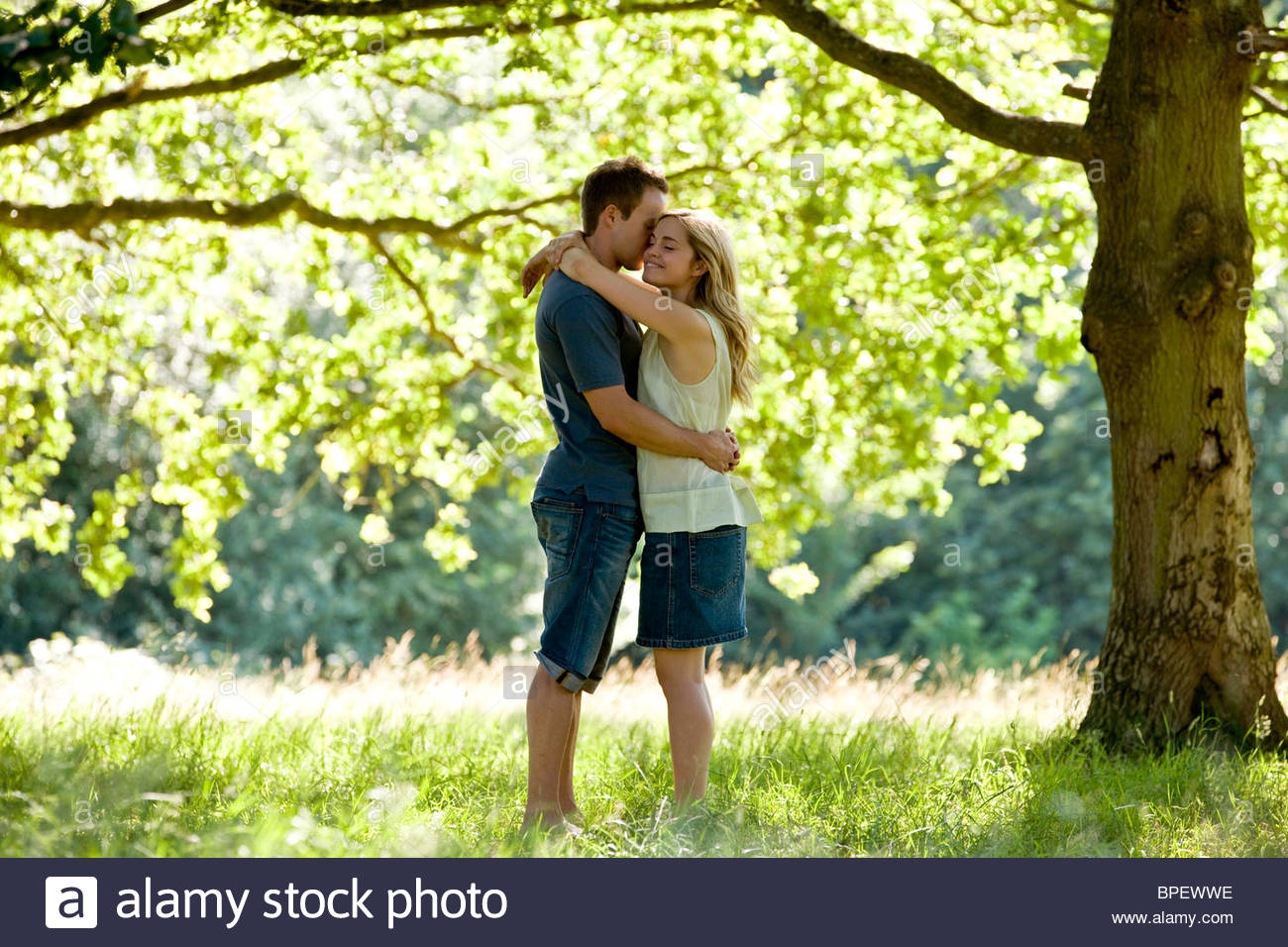 A young couple standing beneath a tree, embracing - Stock Image