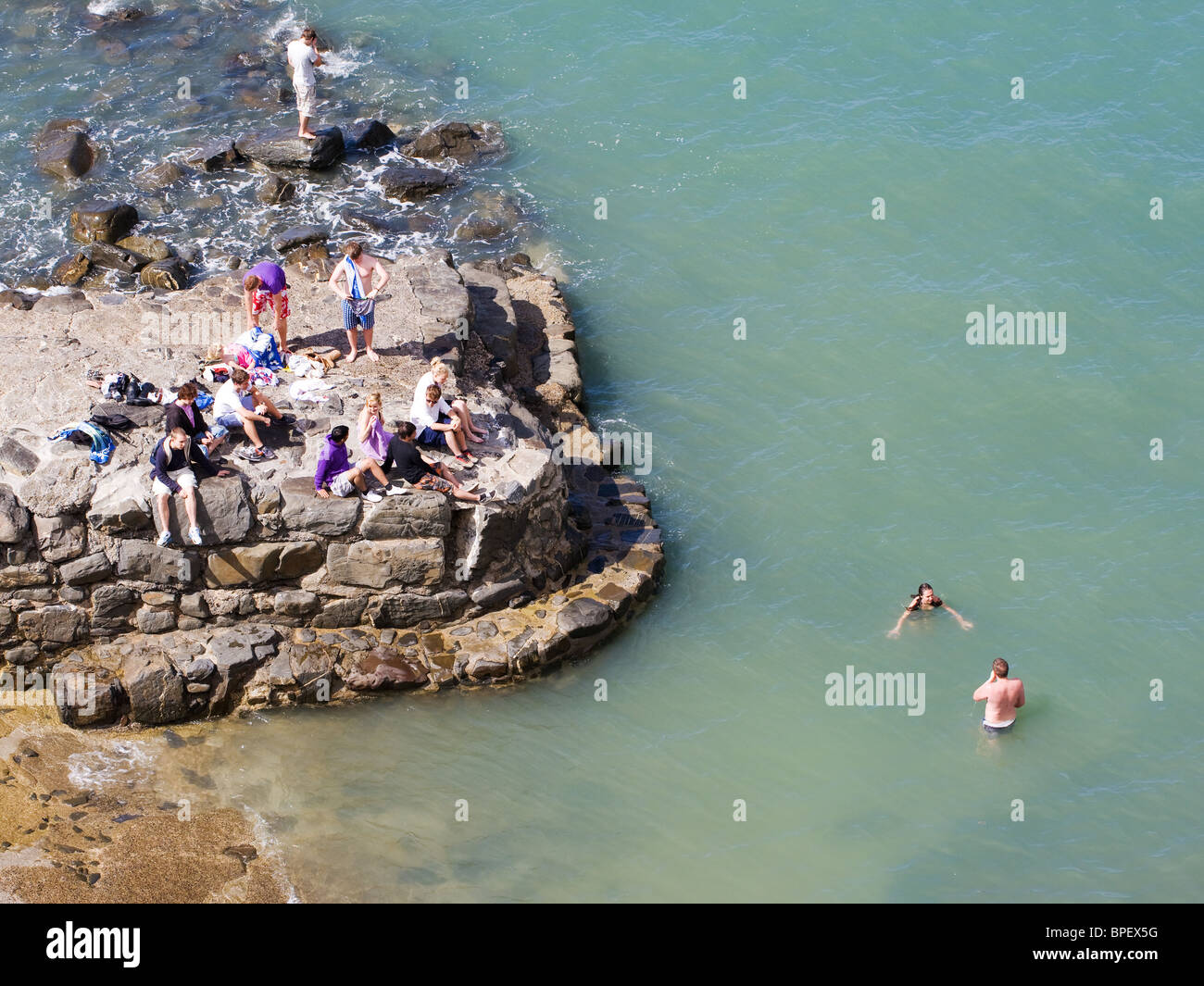 Young bathers swimming in the sea at Hartland Quay on the North Devon coast - Stock Image