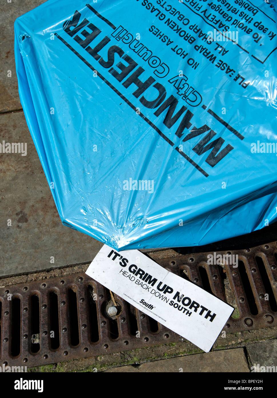 Refuse sack alongside sign saying 'It's Grim Up North' - Stock Image