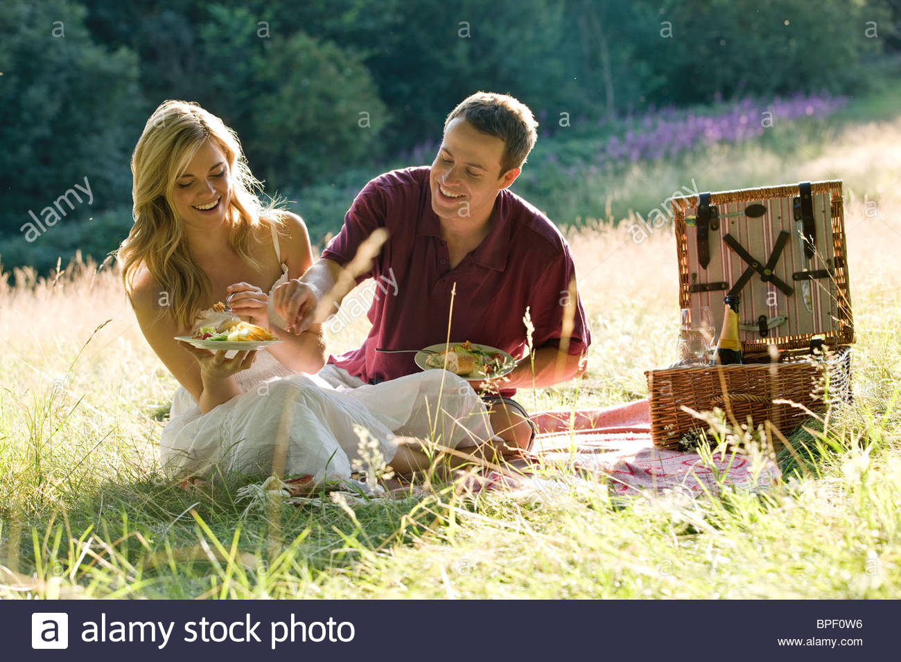 A young couple sitting on the grass, having a picnic - Stock Image