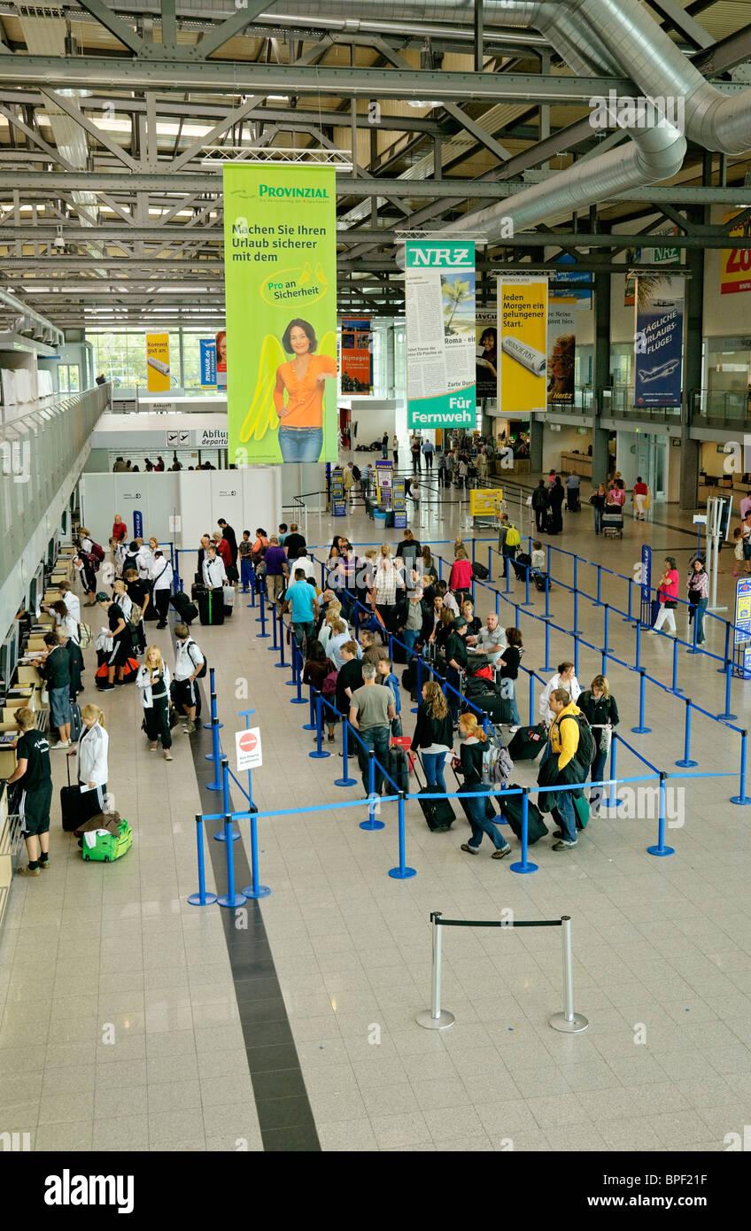 Passenger queuing in terminal building at Weeze (Niederrhein) Airport, North Rhine-Westphalia, Germany. - Stock Image