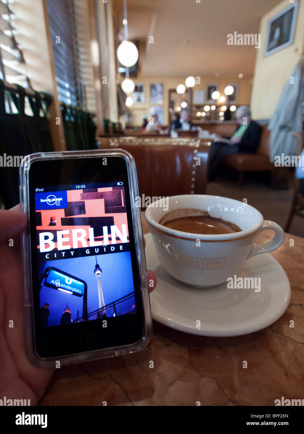 Tourist using e-book travel guide to Berlin in famous Cafe Einstein on Unter den Linden in Berlin Germany Stock Photo