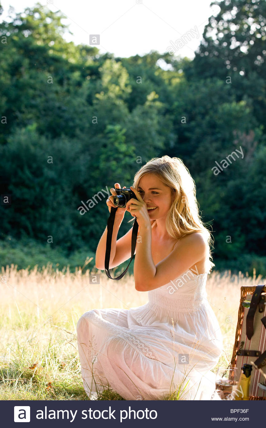 A young woman taking a picture - Stock Image