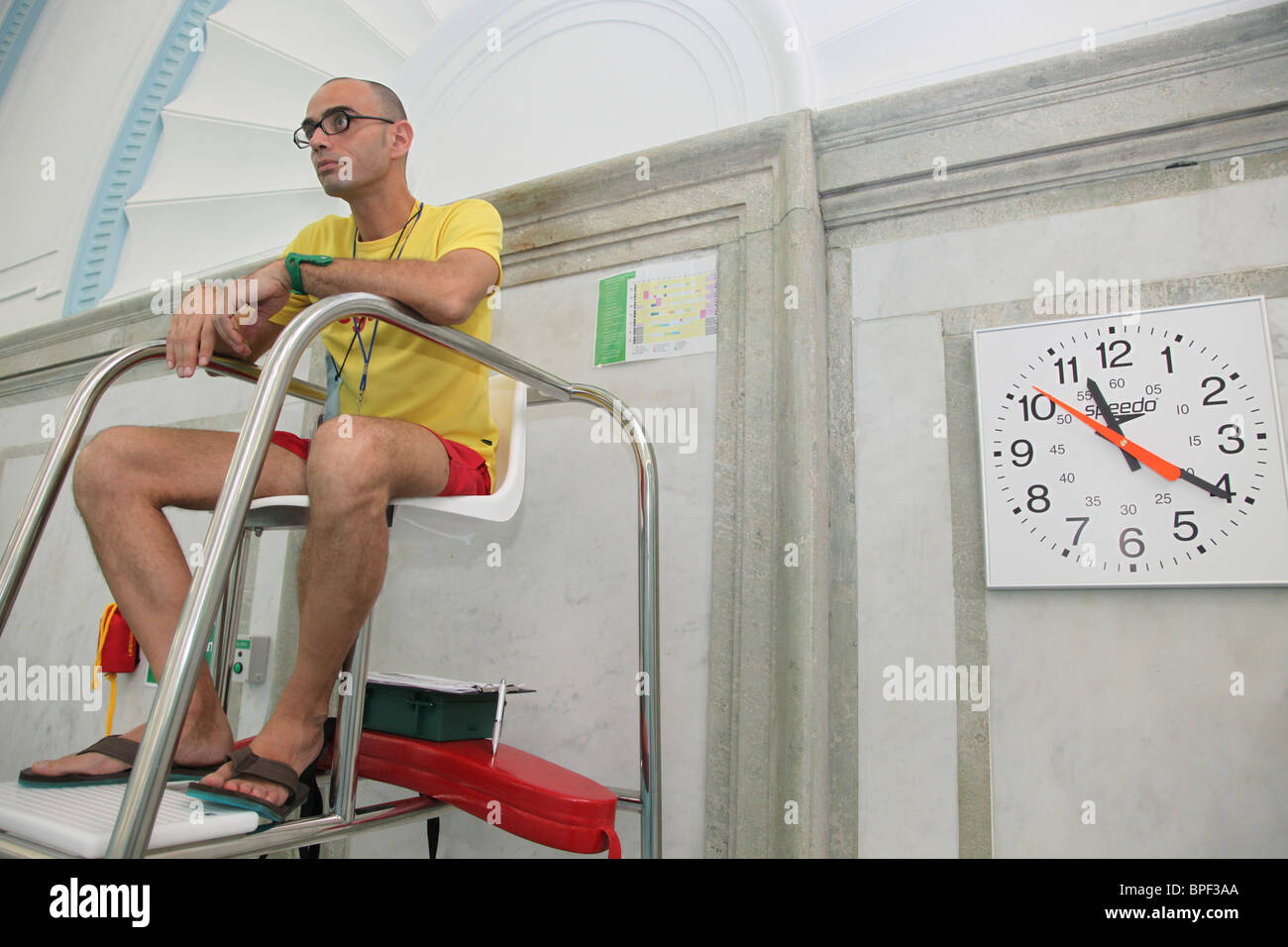 Lifeguard on duty in an indoor swimming pool - Stock Image