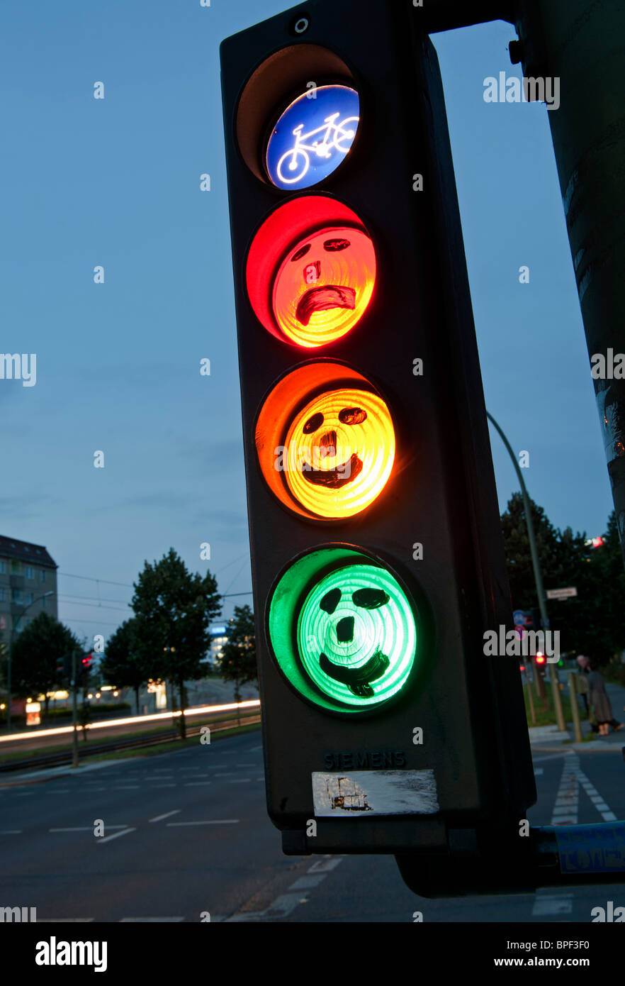 faces drawn onto cycle traffic lights at dusk in Berlin Germany - Stock Image