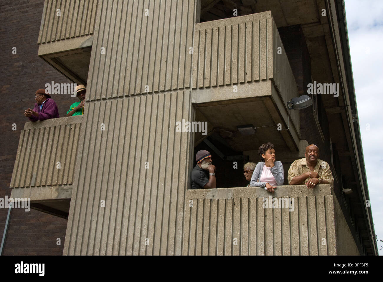 Residents in West London housing estate on their balconies watching Notting hill carnival going by. - Stock Image