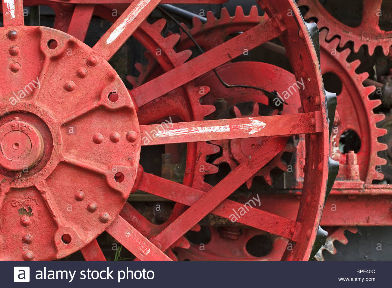 Red gears on a vintage threshing machine. - Stock Image