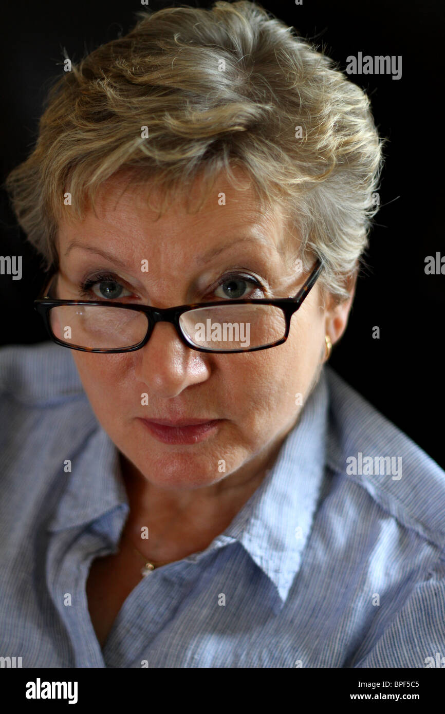 woman in glasses against a dark background - Stock Image