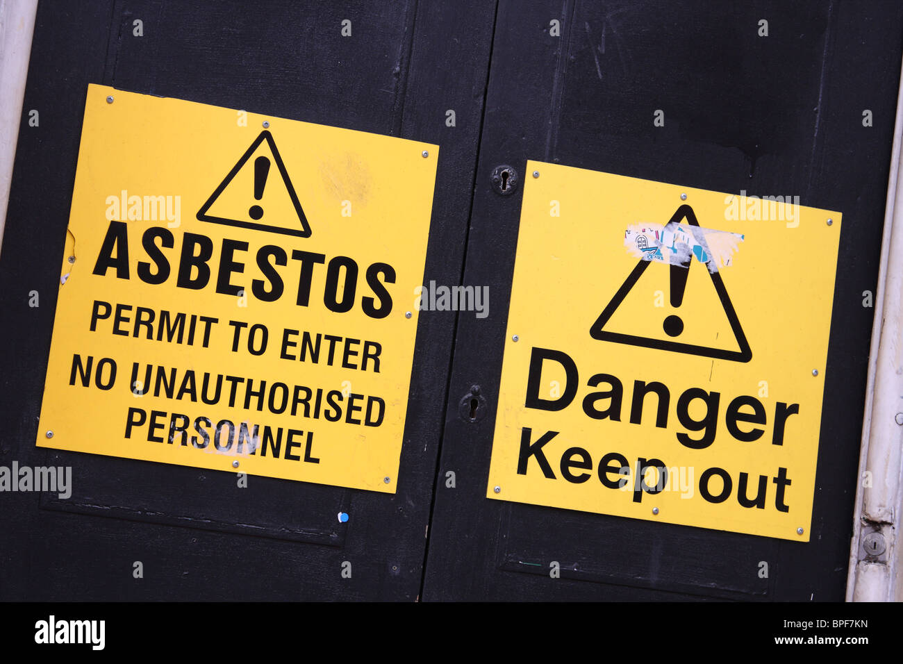 Asbestos warning signs on a derelict building in a U.K. city. - Stock Image