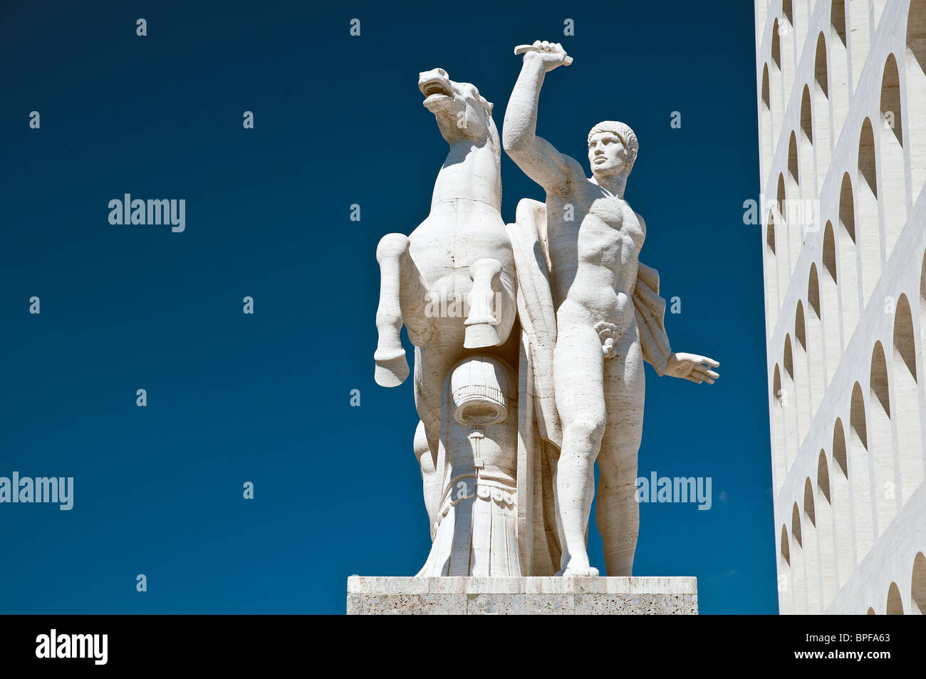 An equestrian sculptural group next to the Palazzo della Civiltà Italiana building, EUR district, Rome, Italy - Stock Image