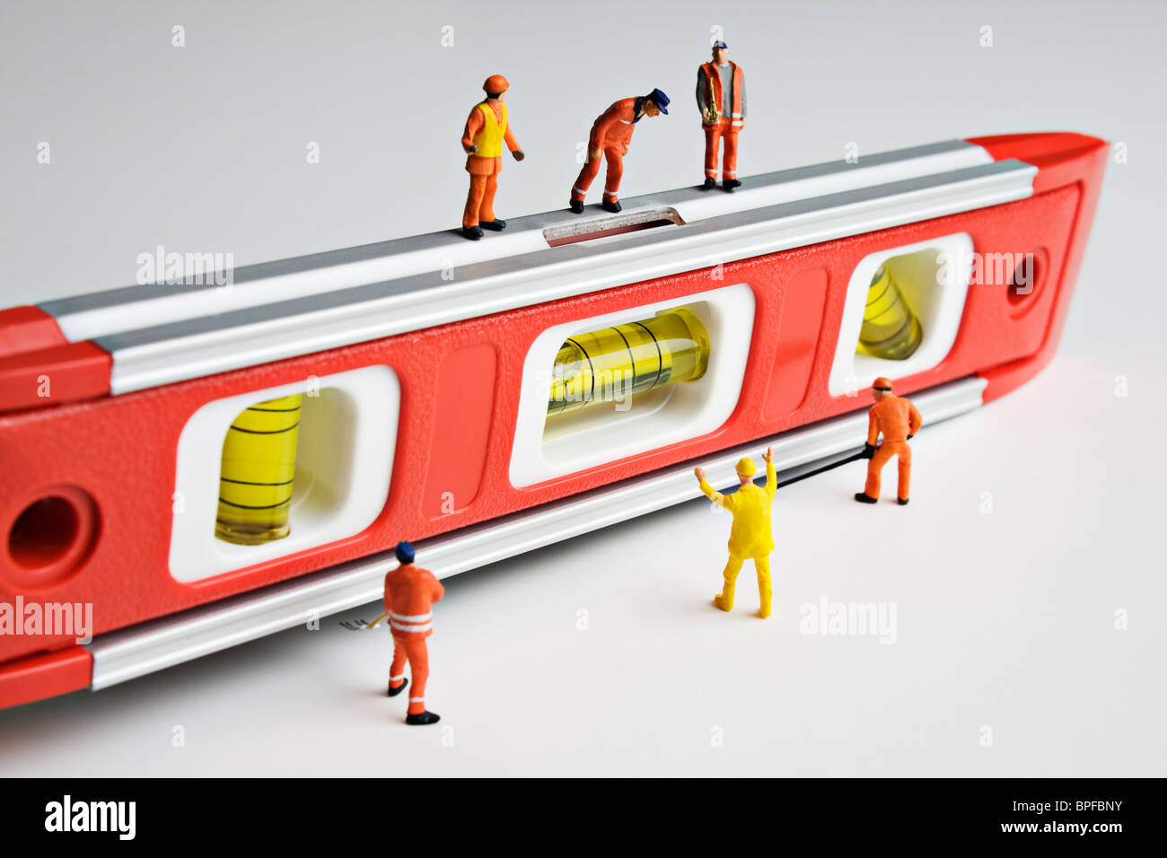 Worker figurines placed on a level - Stock Image