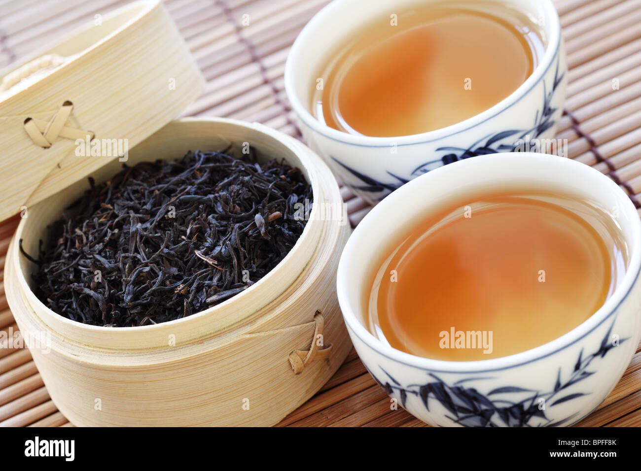 Black tea in a white cup with a tea leafs - Stock Image