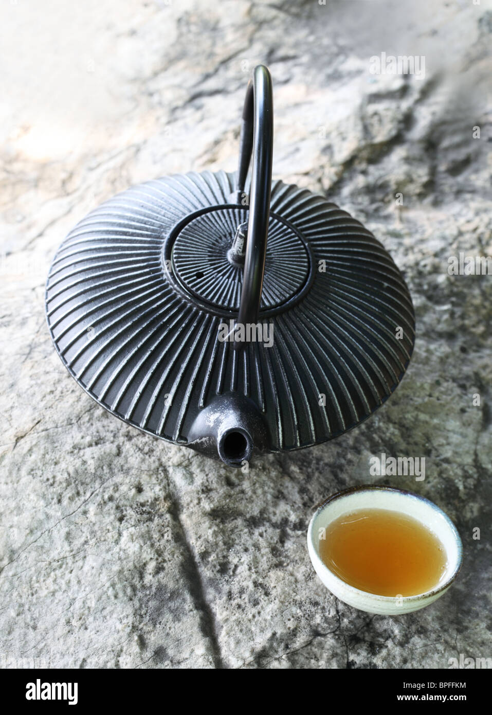 Black iron asian teapot with cup of tea on rock,Closeup. - Stock Image