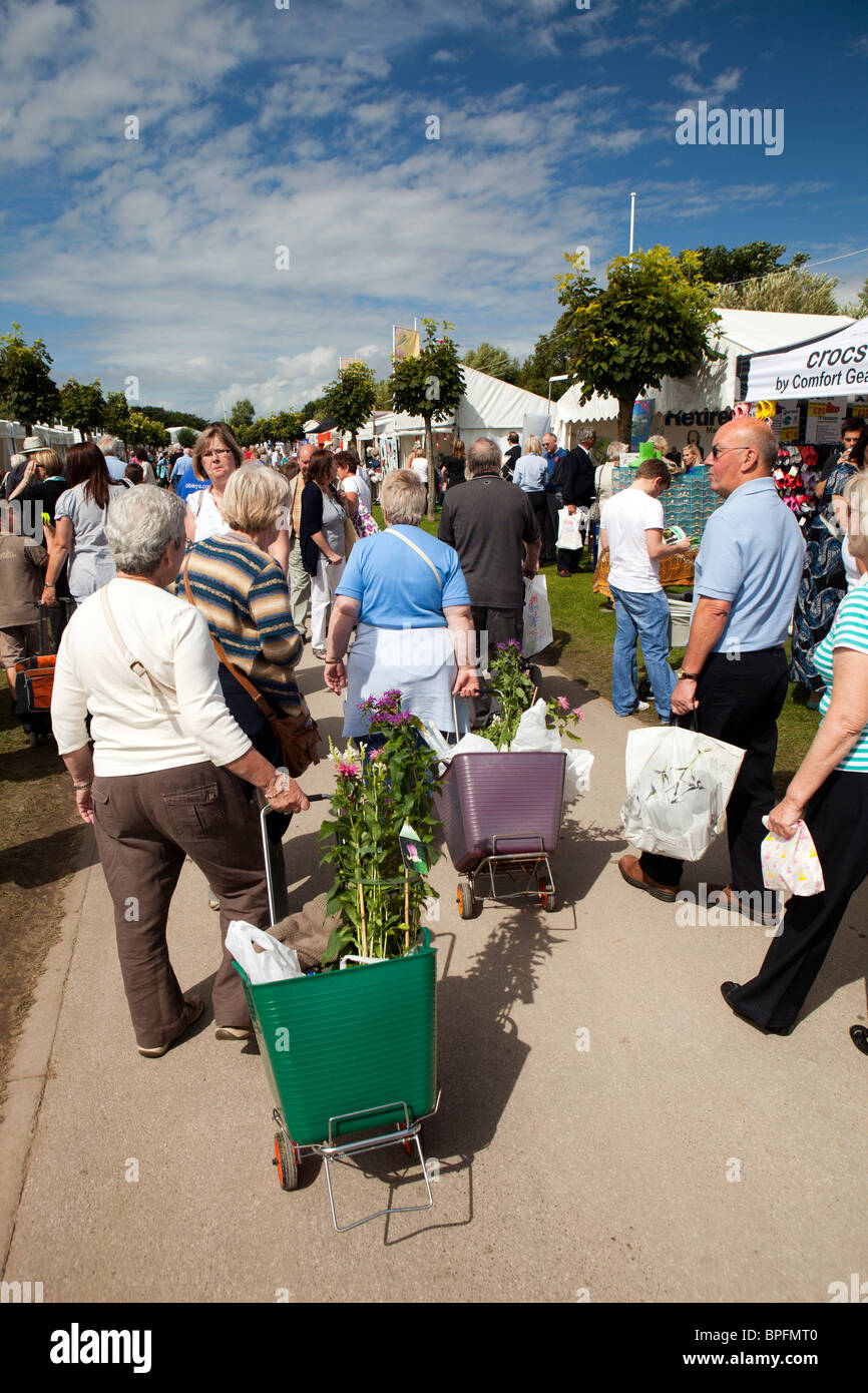 UK, England, Merseyside, Southport Flower Show, visitors carrying bought plants in wheeled shopping baskets Stock Photo