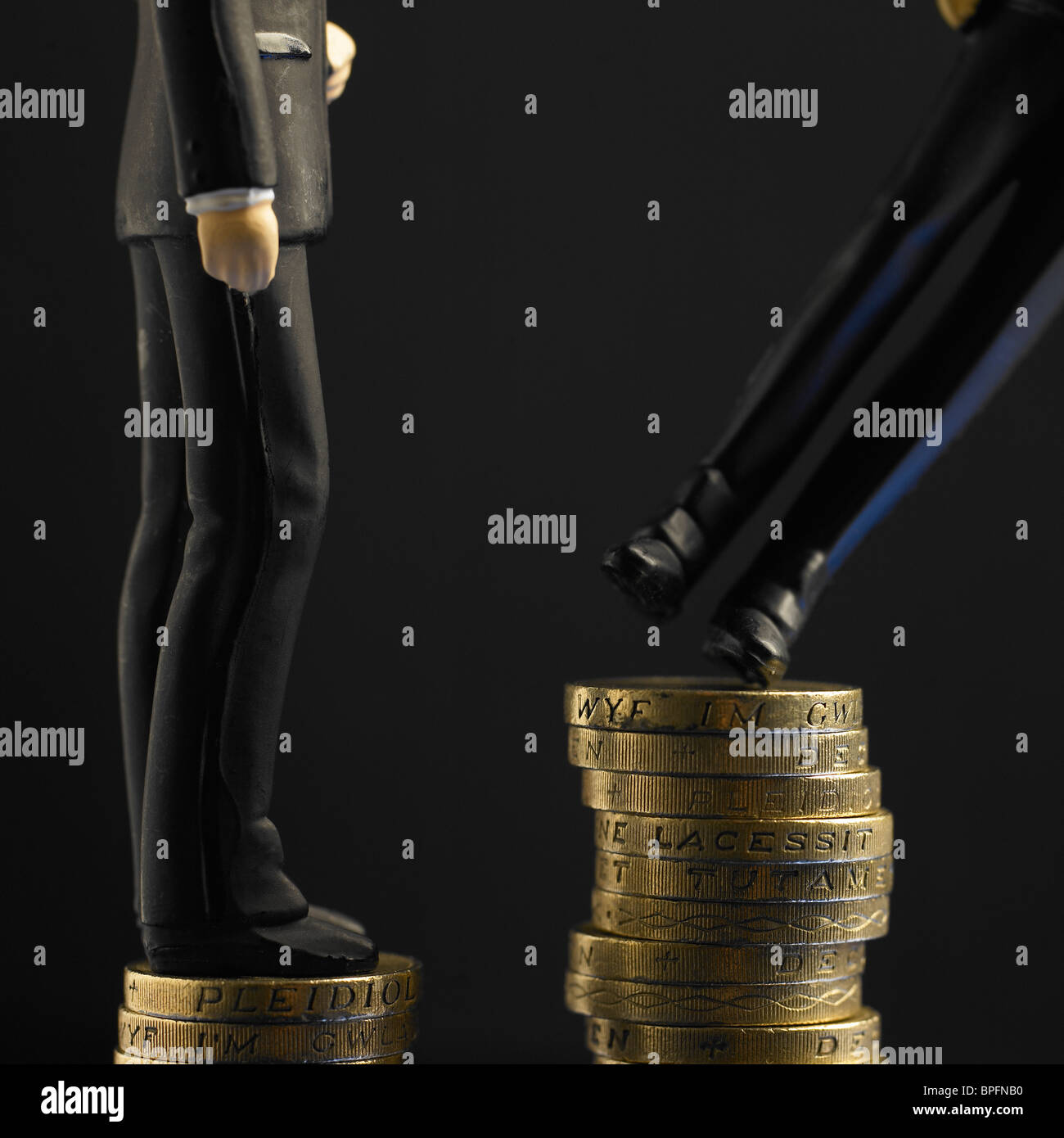 Two Figures In Black Suits Standing On Top Of Unequal Piles Of Pound Sterling Coins, One Toppling Stock Photo