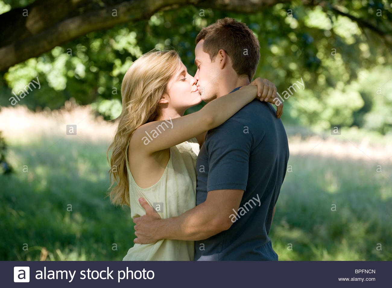 A young couple standing beneath a tree, kissing - Stock Image