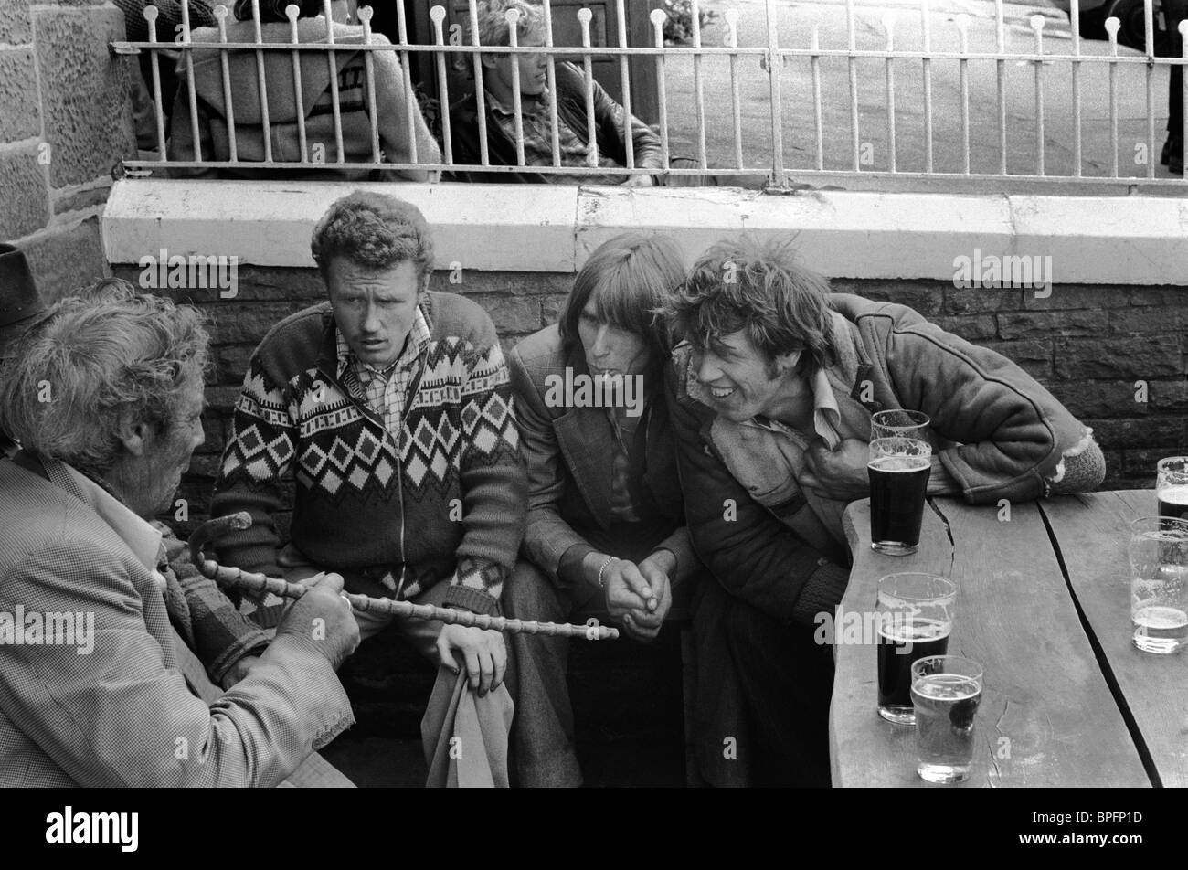 Older gypsy man telling tall story to three younger gypsies . Appleby Gypsy Fair 1981. man talking in pub at Appleby. - Stock Image