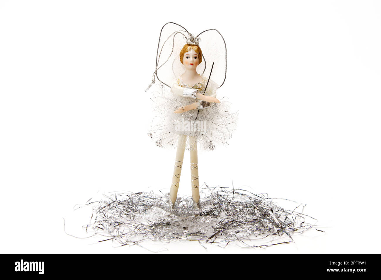 White and silver treetop fairy Christmas ornament standing on tinsel on a white background - Stock Image