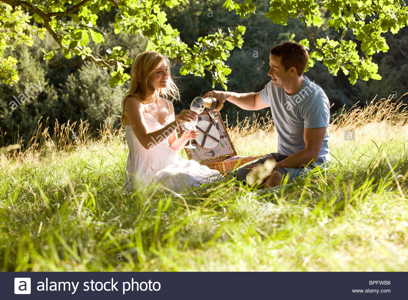 A young couple having a picnic, man pouring sparkling wine - Stock Image