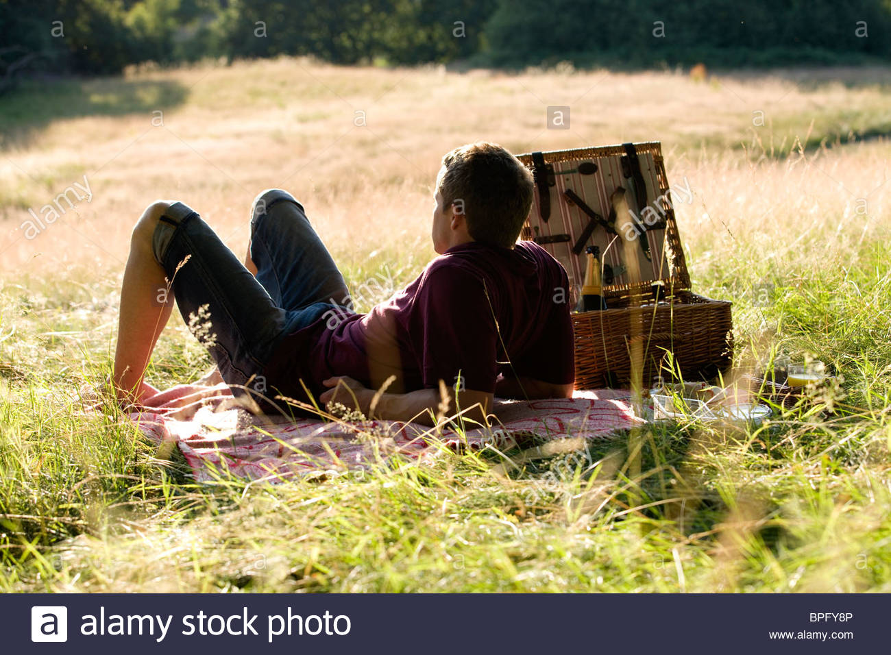 A young man sitting on the grass, having a picnic - Stock Image