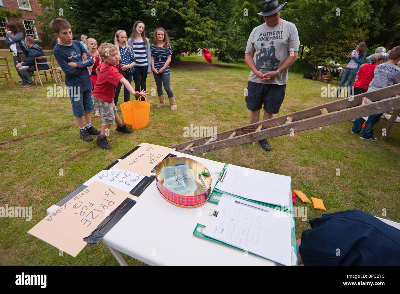 A boy throws a beanbag on a ladder game at a village fete in Weston , Suffolk , England , Great Britain , Uk - Stock Image