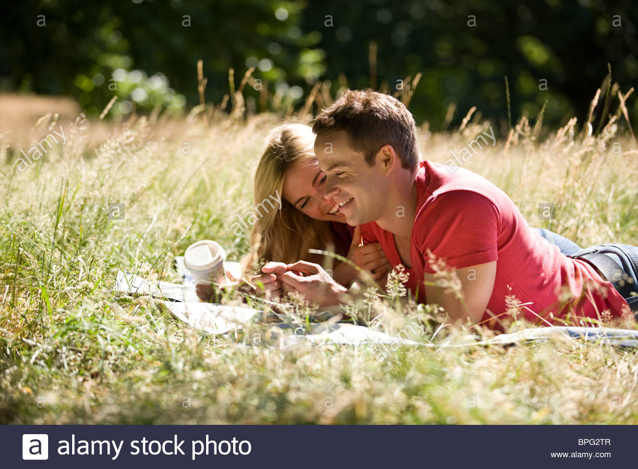 A young couple lying in the grass, relaxing Stock Photo