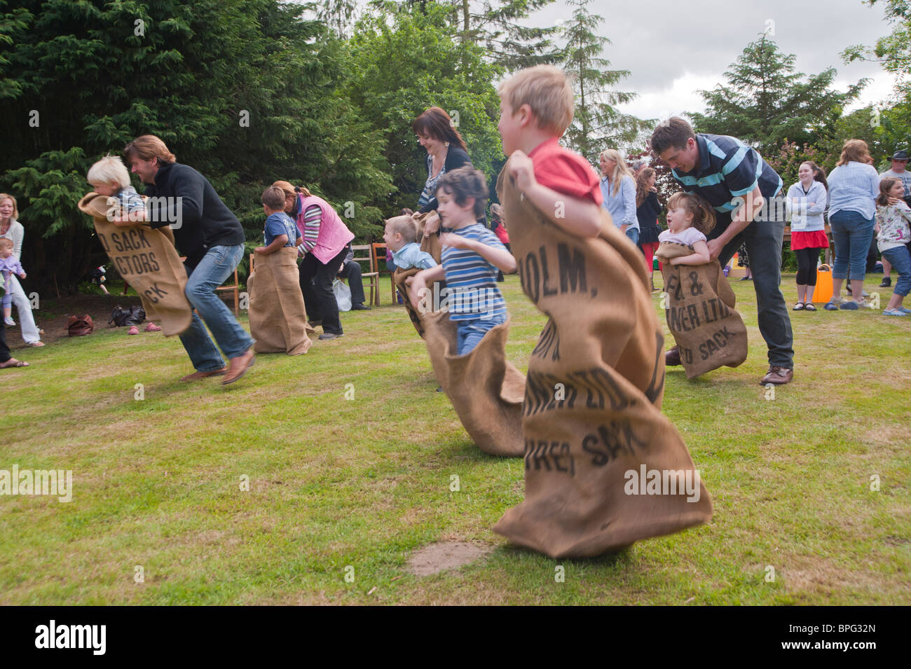 Children compete in the sack race showing movement at a village fete in Weston , Suffolk , England , Great Britain Stock Photo