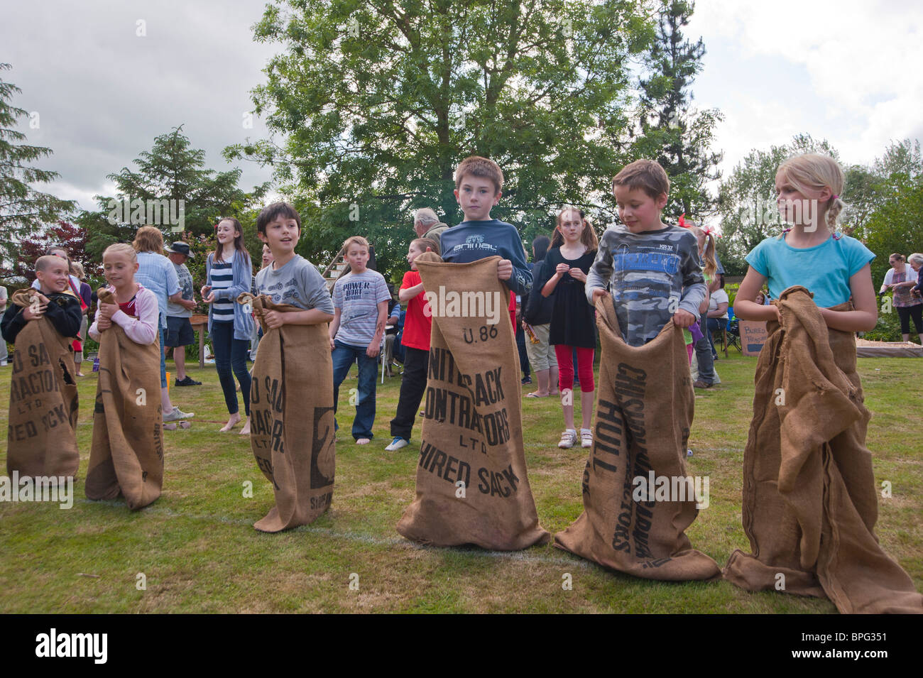 Children compete in the sack race at a village fete in Weston , Suffolk , England , Great Britain , Uk - Stock Image
