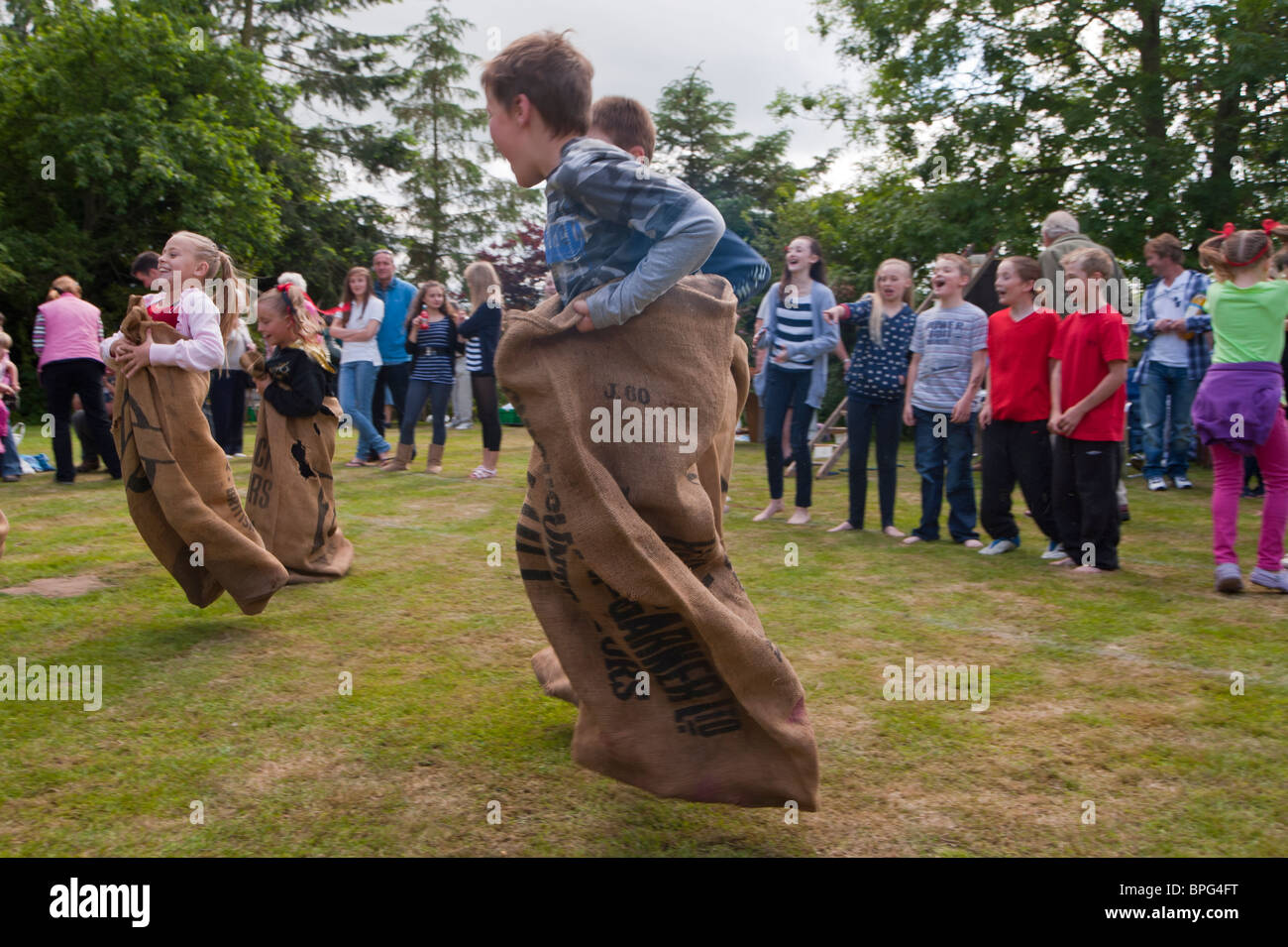 Children compete in the sack race showing movement at a village fete in Weston , Suffolk , England , Great Britain - Stock Image