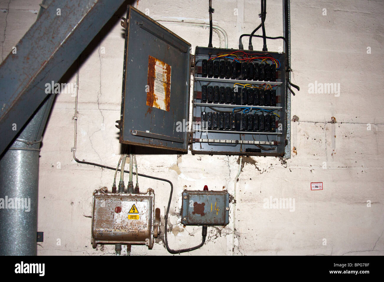 Electrical control panel in a derelict factory, wires and switches everywhere - Stock Image
