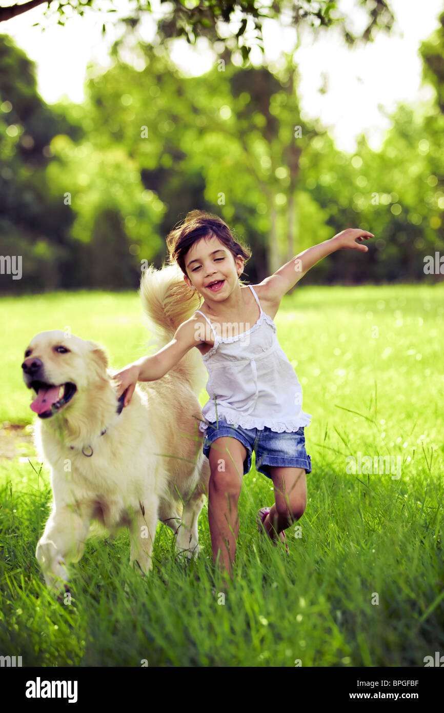 Young girl with golden retriever running outdoors - Stock Image