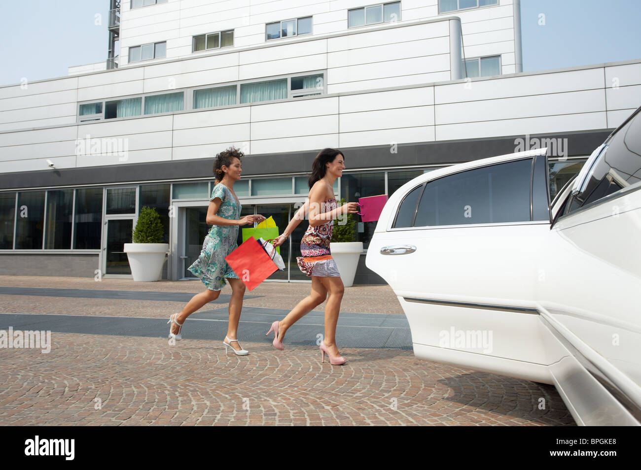 women running into car with shopping bags Stock Photo