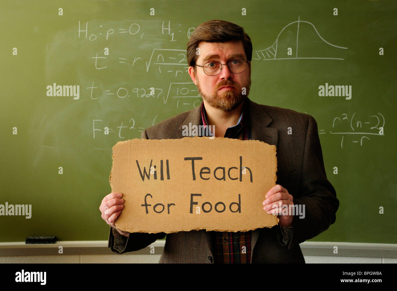 Professor or teacher in classroom holding a 'Will Work for Food' sign. Statistical formula on chalkboard - Stock Image