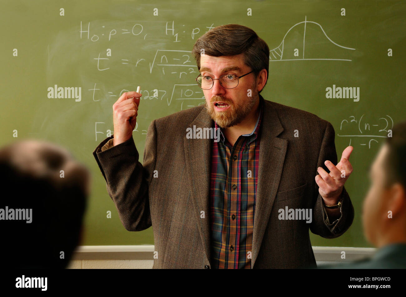 Math professor or teacher interacting with students in a classroom, Statistical formula on chalkboard in background. - Stock Image