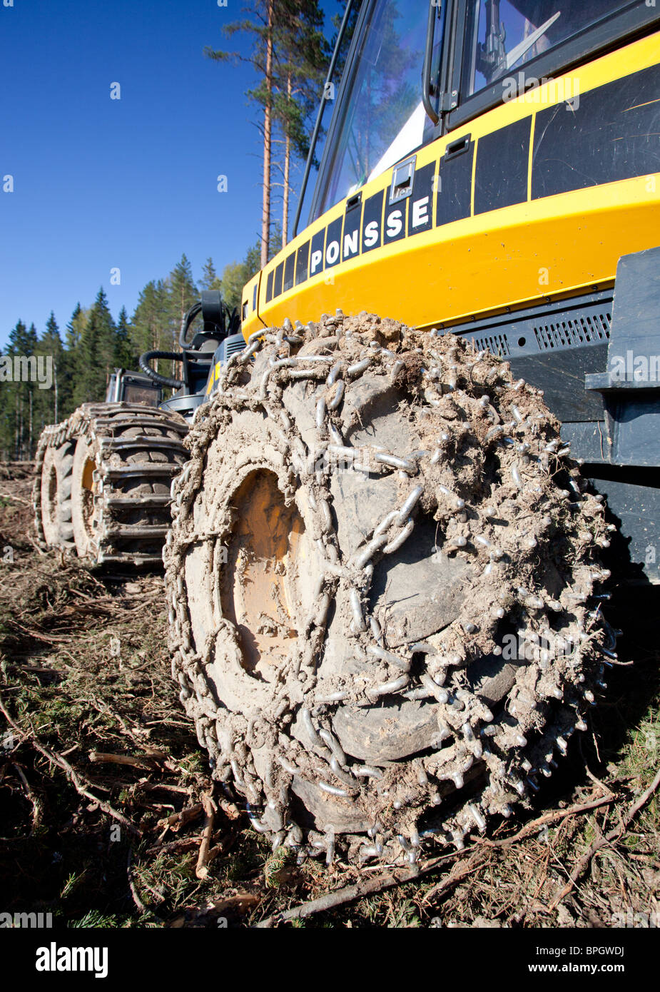 Dirty Ponsse Beaver forest harvester tyres with tire chains - Stock Image