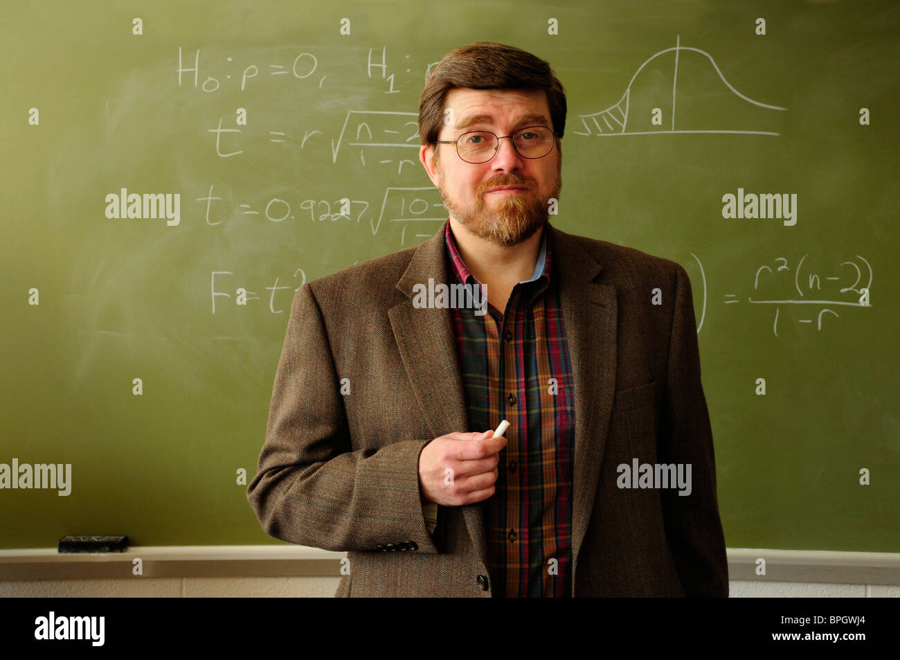 Math professor or teacher standing in a classroom, Statistical formula on chalkboard in background. - Stock Image