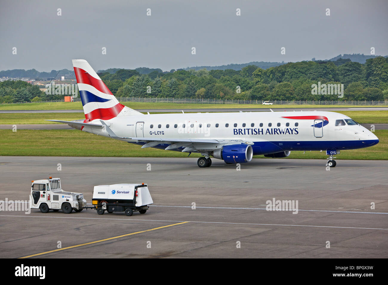 BA Cityflyer G-LCYG Embraer E170 STD at Edinburgh Airport with ancillary vehicle to fore - Stock Image