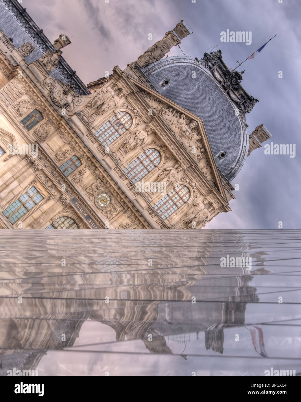 The Louvre reflects from I.M. Pei's Pyramid, as storm clouds gather above. One wall of the Pyramid forms a false Stock Photo