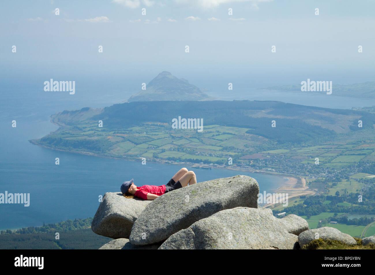 A sunbather on the summit of Goatfell, Isle of Arran, Scotland - Stock Image