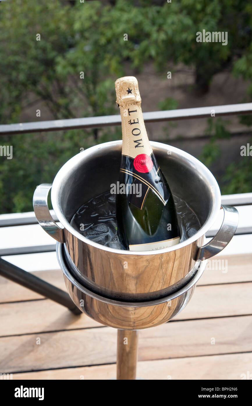 unopened bottle of Moet & Chandon champagne cooling in a bucket of ice at rooftop bar of trendy upscale hotel - Stock Image