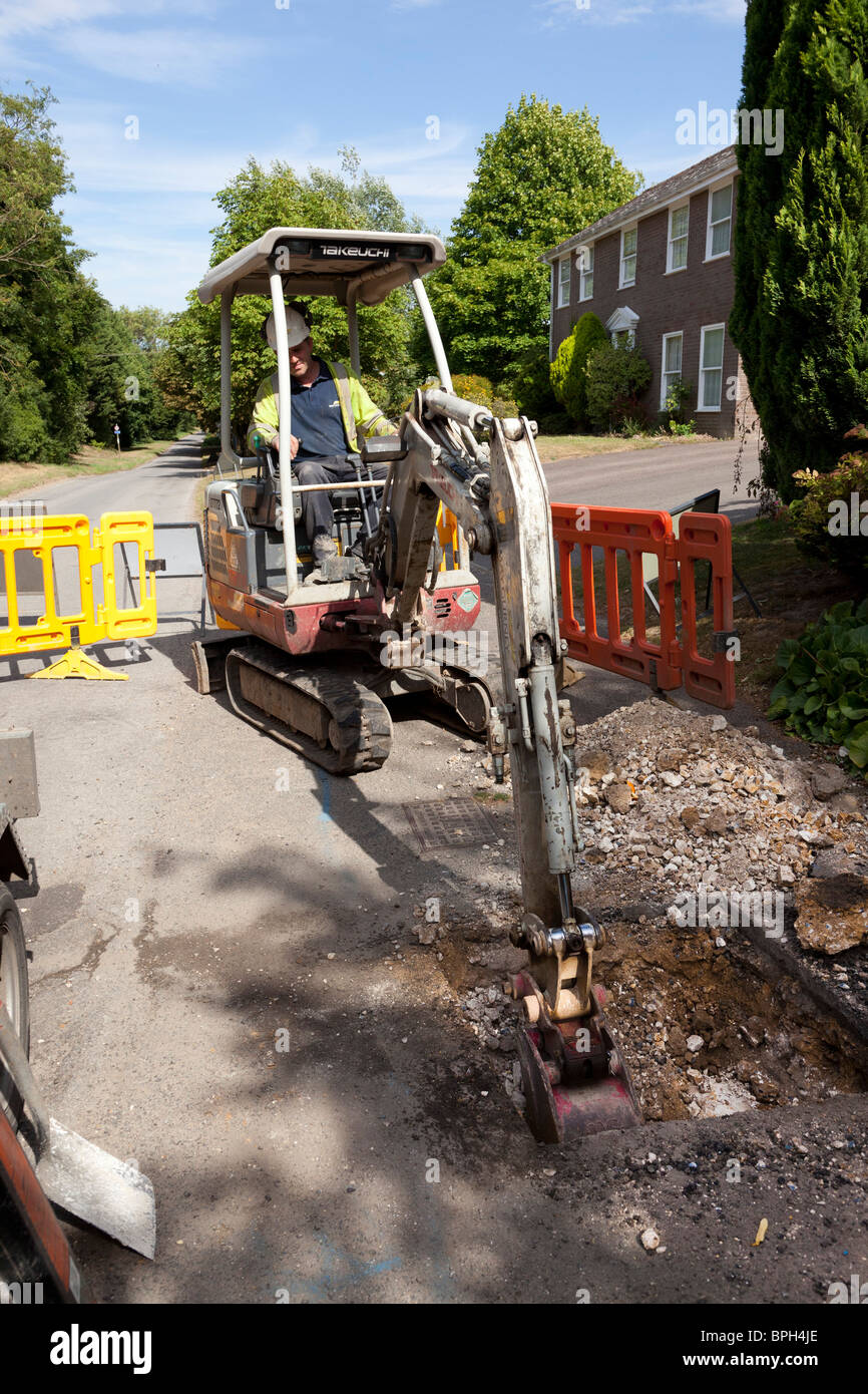 workers using a mini excavator to dig a trench in the road - Stock Image