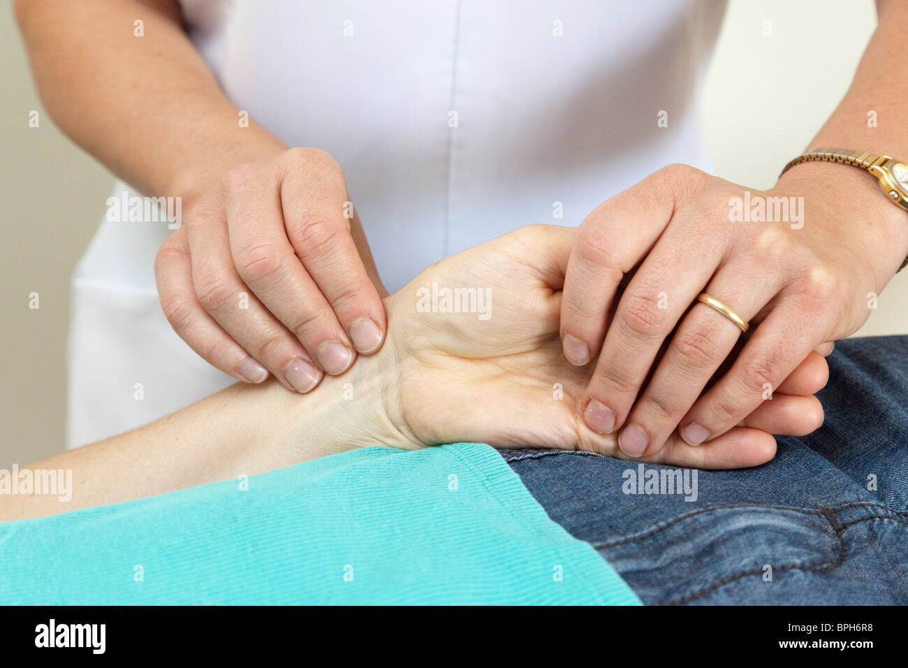 nurse checking a patient's heartbeat pulse in wrist - Stock Image