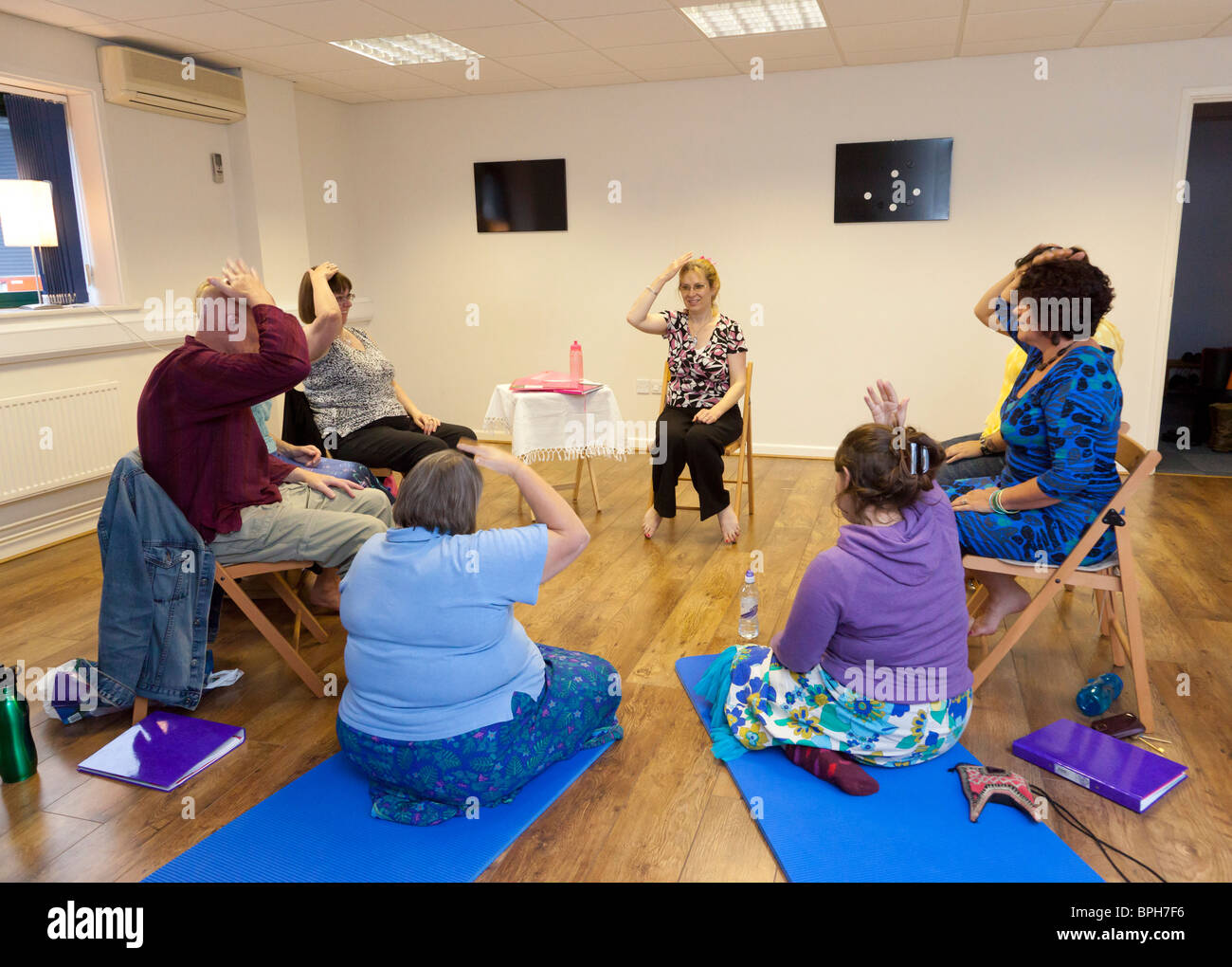 a class being taught the Emotional Freedom Technique - Stock Image